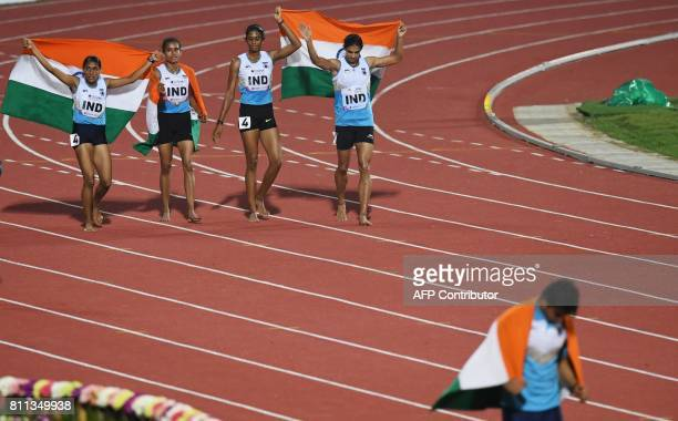 India's women's 4 x 400m relay team and India's javelin athlete Neeraj Chopra celebrate placing first during the final day of the 22nd Asian...
