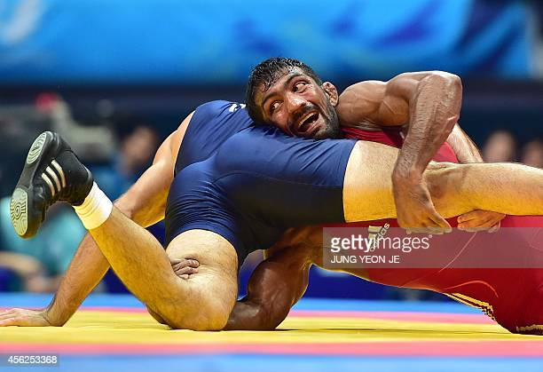 India's Yogeshwar Dutt competes with Tajikistan's Zalimkhan Yusupov in the men's freestyle 65 kg wrestling event for the gold medal during the 2014...