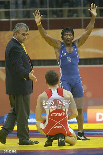 India's Yogeshwar Dutt, in blue, celebrates after beating Canada's James Mancini to win the gold medal in the men's freestyle 60kg wrestling finalsat...