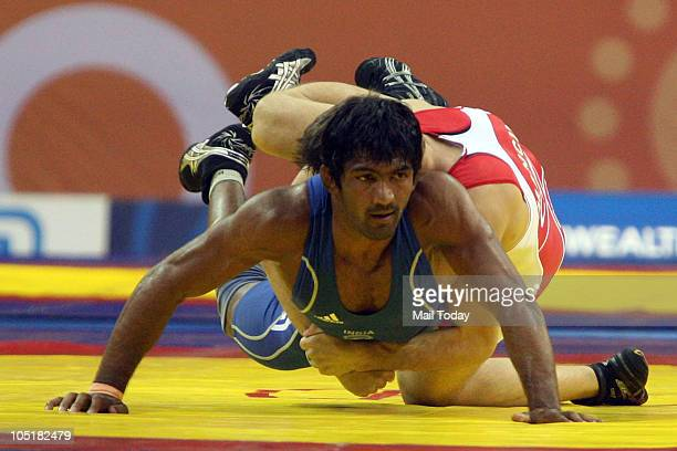 India's Yogeshwar Dutt muscles his way past James Mancini of Canada to win gold in the 60kg freestyle category during the Commonwealth Games 2010 at...