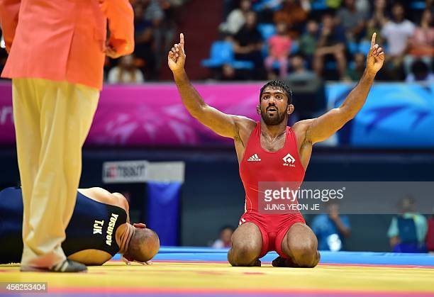 India's Yogeshwar Dutt reacts after winning the match against Tajikistan's Zalimkhan Yusupov in the men's freestyle 65 kg wrestling event for the...