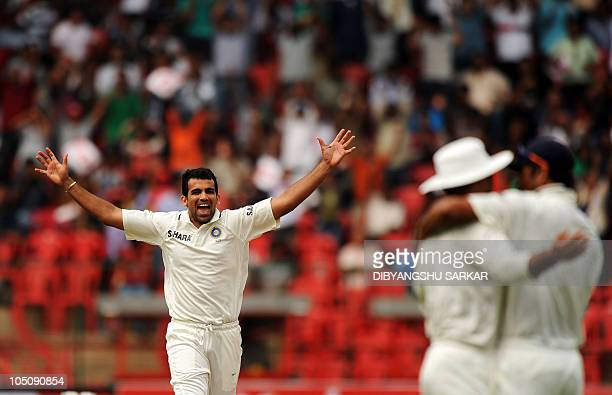 India's Zaheer Khan celebrates the wicket of Australia's Michael Hussey as India's Rahul Dravid congratulates Virender Sehwag for taking the catch...