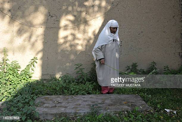 India-unrest-Kashmir-rights,FEATURE by Izhar Wani In a picture taken on October 10 Zoona Bugum , sweeps the grave of her daughter,Mqbool Shah, in...