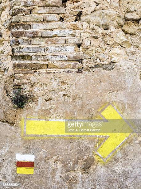Indications of colors painted on an ancient wall in the mountains, indication of colors and path arrow GR