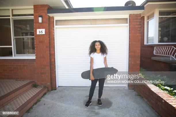 Indigenous Aboriginal teenage girl with skateboard standing in front of garage.