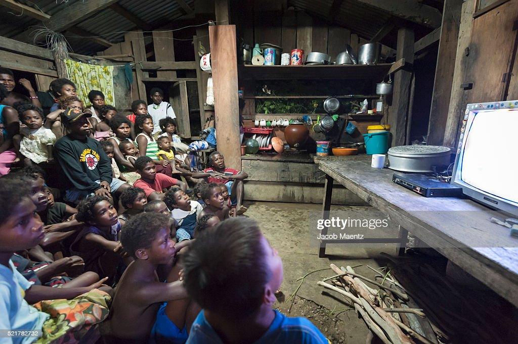 Indigenous Agta watch television together with electricity powered by a generator : Stock Photo