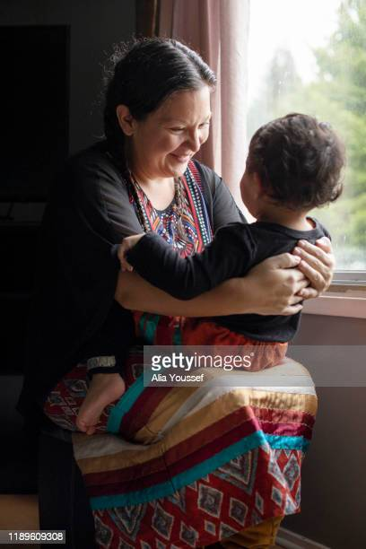indigenous artist and mother with her daughter at home - showus stock pictures, royalty-free photos & images