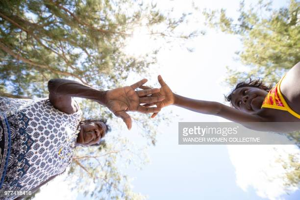 Indigenous Australian Aboriginal grandmother elder and child holding out hands to each other