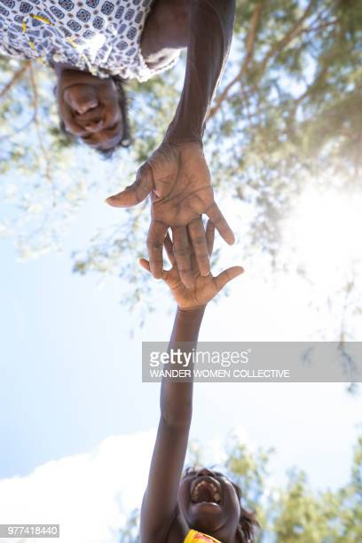 Indigenous Australian Aboriginal grandmother elder and child holding out hands to each other laughing