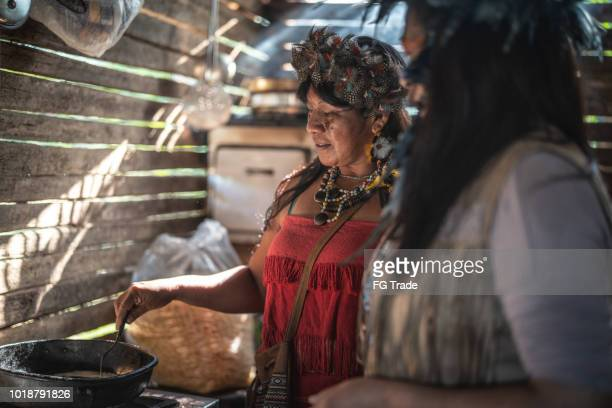 "indigenous brazilian women, from guarani ethnicity, cooking ""xipa"" - indigenous culture stock pictures, royalty-free photos & images"