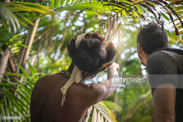 Indigenous Brazilian Young Man from Guarani ethnicity Showing the Rainforest to Tourist