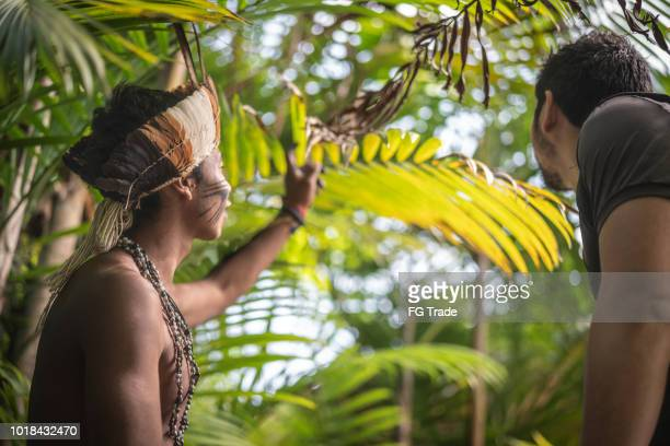 indigenous brazilian young man from guarani ethnicity showing the rainforest to tourist - handsome native american men stock pictures, royalty-free photos & images