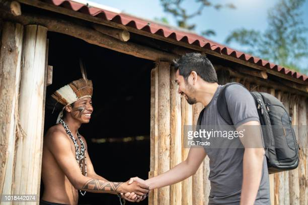 indigenous brazilian young man portrait from guarani ethnicity, welcoming the tourist - indigenous culture stock pictures, royalty-free photos & images
