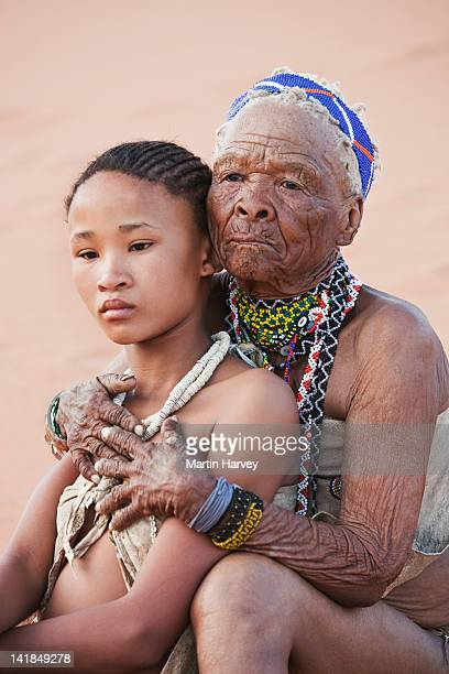 indigenous bushman/san girl embraced by grandmother (14years old, 75 years old), namibia (image taken to raise awareness and funds for the conservation projects of n/aâ¿an k - 14 15 years stock pictures, royalty-free photos & images