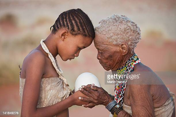indigenous bushman/san girl given ostrich egg by grandmother (14years old, 75 years old), namibia (image taken to raise awareness and funds for the conservation pr - minderheit stock-fotos und bilder
