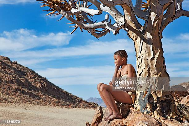 indigenous bushman/san girl (14 -15 years old) under quiver tree (aloe dichotoma), namibia (image taken to raise awareness and funds for the conservation projects of n/a''an ku - 14 15 years stock pictures, royalty-free photos & images