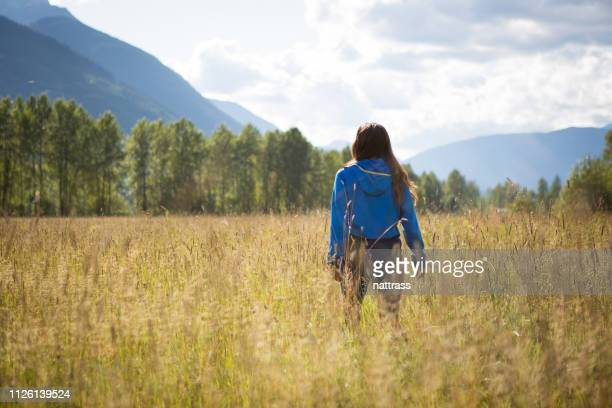 indigenous canadian woman walking in the field - first nations stock pictures, royalty-free photos & images