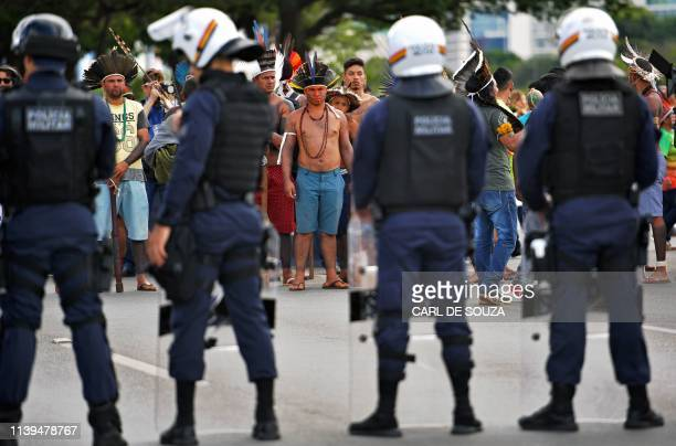 Indigenous demonstrators stand in front of riot police during a protest march to defend indigenous land and rights in Brasilia Brazil on April 26 on...
