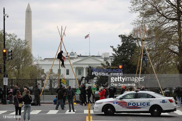 Indigenous environmental activists suspend themselves from large tripods, blocking traffic near Black Lives Matter Plaza on the north side of the...