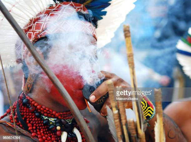 Indigenous face painted man with smoke around his head.
