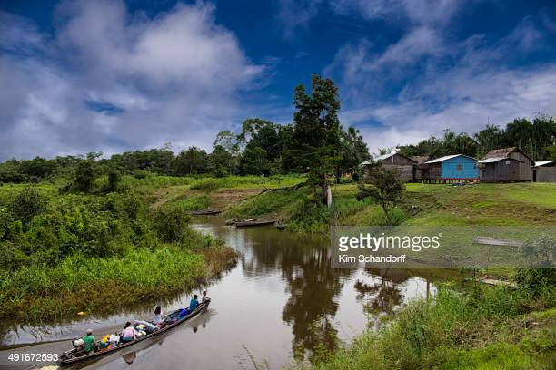 Indigenous families arriving at a village in the Amazon jungle in Peru.