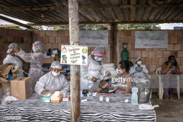 Indigenous healthcare workers wearing personal protective equipment treat patients at the Indian campaign hospital set up in the Parque das Tribos...