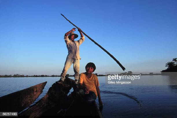 Indigenous Indians father and son fish on a hand made wooden boat June 1999 in the Amazon basin Bolivia