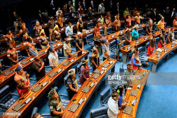 Indigenous leaders occupy senators' seats during a plenary session of the Brazilian Sederal Senate in homage to indigenous people in Brasilia on...