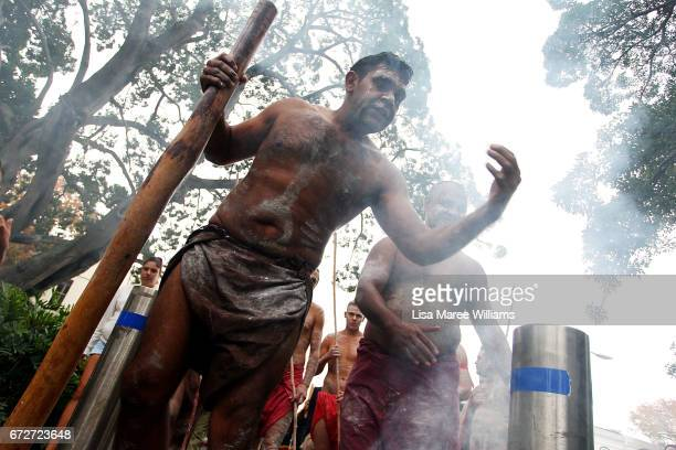 A indigenous man takes part in a traditional smoking ceremony during the ANZAC service at Redfern Park on April 25 2017 in Sydney Australia The...