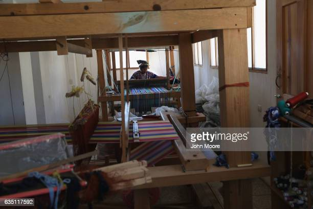 Indigenous Mayan weaver Delfina Perez who's husband has worked in the US as an immigrant for 20 years works on a foot loom at the Grupo Cajola...