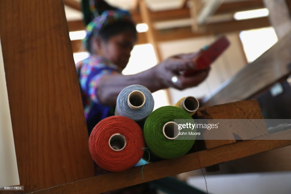 Indigenous Mayan weaver Delfina Perez, who's husband has worked in the U.S. as an immigrant for 20 years, works on a foot loom at the Grupo Cajola weaving cooperative on February 11, 2017 in Cajola, Guatemala. Women are especially effected by emigration from Guatemala, where some 70 percent of the men have left to work as undocumented immigrants in the United States, many of them leaving behind wives and children who only know their fathers online, if at all. Grupo Cajola, an NGO funded by American donations, is attempting to make the town's economy prosper locally to help reduce the need for emigration. With U.S. President Donald Trump's crackdown on illegal immigration, the spectre of increased deportations back to Guatemala and reduced remittances has made the need to educate both children and adults and transform the local economy more urgent than ever. Remitances from undocumented Guatemalan laborers are the main source of income of Guatemala, and while increasing wealth and driving a housing boom in towns like Cajola, they have also had the negative effect tearing the social fabric of local communites. Grupo Cajola has set up a weaving center, an egg farm, carpentry shop, internet cafe, library and education programs for pre-schoolers and their parents, while providing scholarships for more than 20 young residents to learn local trades. Textiles they produce are now exported for sale to the U.S. The NGO was founded in 2000 by Eduardo Jimenez, who lived as an undocumented immigrant for 10 years in the U.S. before returning to Guatemala. He coordinates locally with the group's American director Caryn Maxim, who organizes funding and product sales in New Jersey.