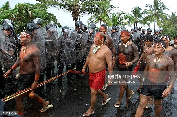 Indigenous members of the Yanomami tribe pass military policemen 22 April 2000 in a march in Coroa Vermelha Brazil Tribe members are marching to...