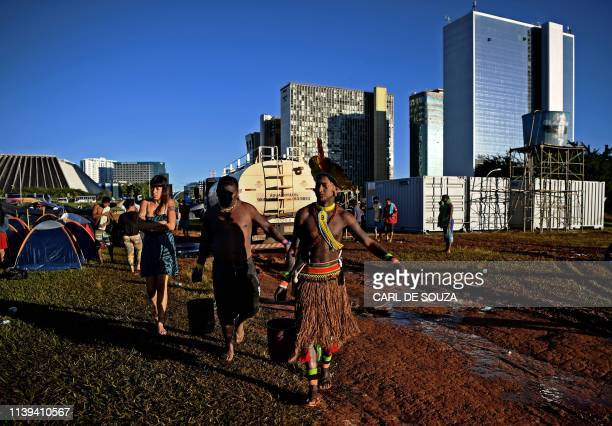 Indigenous men collect water at a protest camp in Brasilia on April 26 2019 Approximately 4000 indigenous people from different tribes are taking...