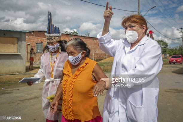 Indigenous nurses wearing protective masks take an elderly woman to make testing at Parque das Tribos community on May 21 2020 in Manaus Brazil...