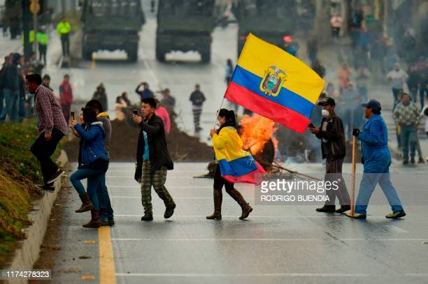 Indigenous people and peasants block a road as they protest against the economic policies of the government of Ecuadorean President Lenin Moreno...