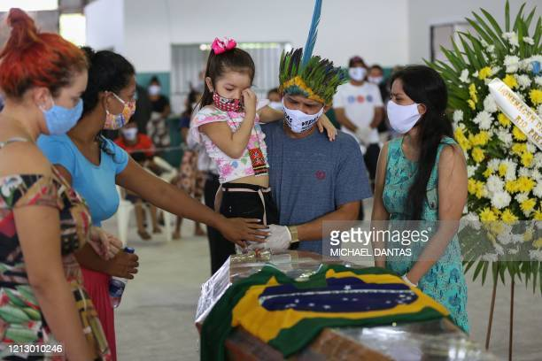 TOPSHOT Indigenous people from the Parque das Tribos community mourn besides the coffin of Chief Messias of the Kokama tribe who died victim of the...