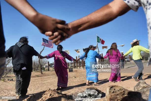 Indigenous people from the Tohono O'odham ethnic group dance and sing to protest against US President Donald Trump's intention to build a new wall in...