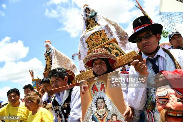 Indigenous people hold religious images as they wait for Pope Francis to arrive for a meeting with thousands of faithfuls in the Peruvian city of...