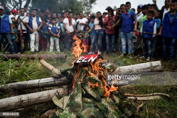 Indigenous people of the Nasa ethnic group burn uniforms seized from ELN guerrillas on July 6 in Corinto Cauca department Colombia Colombian...