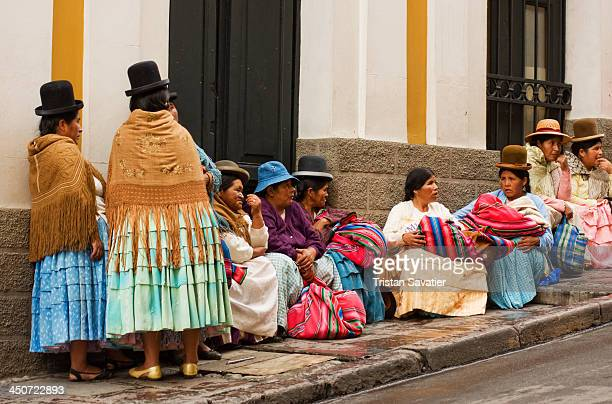 Indigenous Quechua women waiting in front of a Bolivian Government building, in La Paz. Those Quechua women wear the colorful traditional costume,...