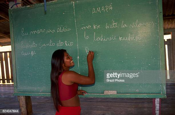 Indigenous school native girl writes on blackboard in classroom Espirito Santo do Rio Curupi Village Karipuna do Amapa Indigenous People Amapa State...
