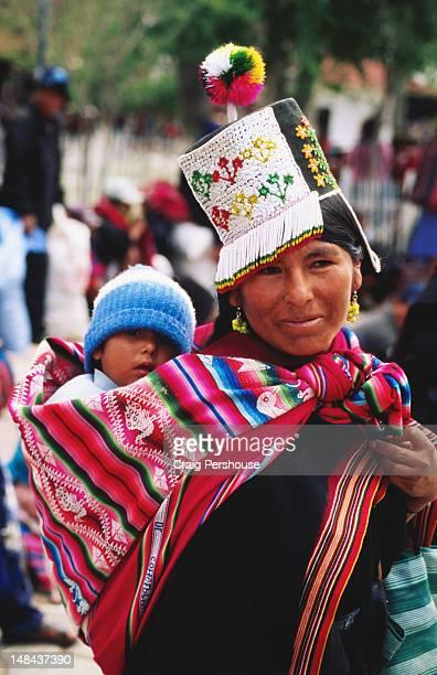 indigenous woman in traditional headwear with baby son. - bolivien stock-fotos und bilder