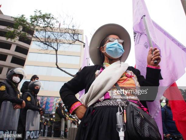 Indigenous woman waving a flag in front of police when on the day of Pedro Castillo's presidential inauguration his supporters take to the streets to...