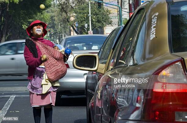 Indigenous woman with her face painted as a clown and carrying her child, juggles on a street in Mexico City on December 30, 2009. Mexico's economy...