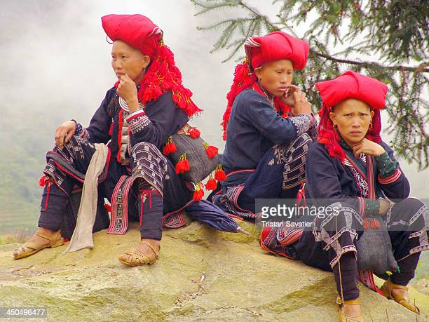 Indigenous women from the Red Dao hill tribe sitting on a rock near the touristic town of Sa Pa in the North of Vietnam. This hill tribe is also...