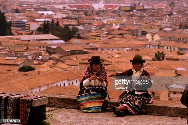 Indigenous women spinning on a flat rooftop Cuzco Peru