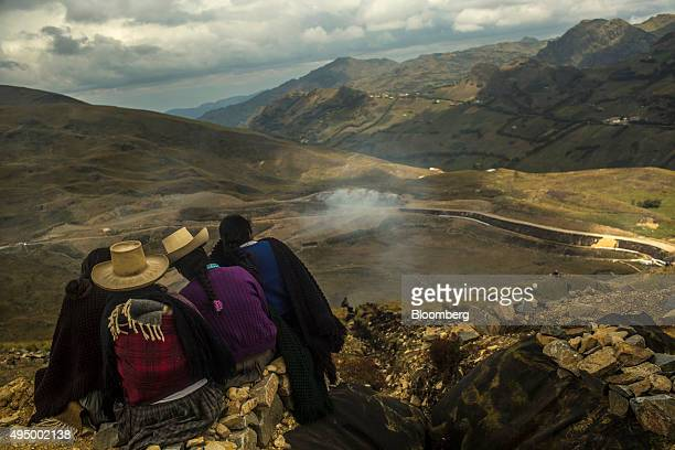 Indigenous women that are part of a protest group look down from a hilltop at smoke rising from containment nets at a water barrier on the property...