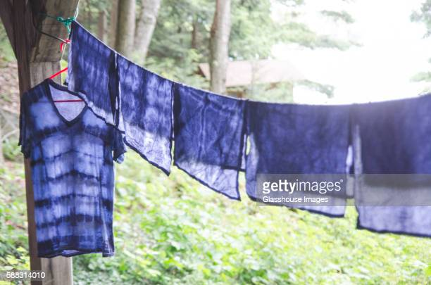 indigo tie-dyed t-shirt and napkins hanging out to dry on clothes line - tie dye stock pictures, royalty-free photos & images