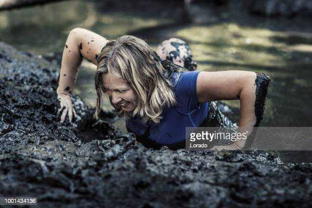 individual beautiful blonde woman having sporty fun at a public mud run obstacle course - obstacle course stock photos and pictures