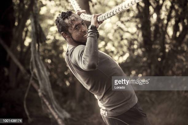 individual non caucasian adult male having sporty fun at a public mud run obstacle course - military training stock pictures, royalty-free photos & images